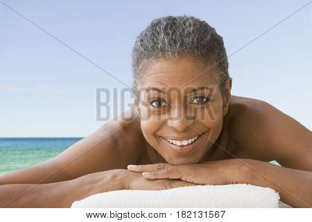 Mixed race woman laying on towel at beach