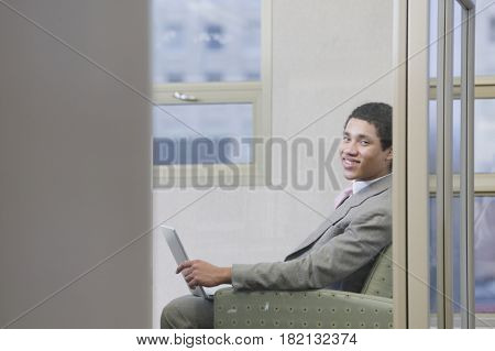 Mixed race businessman working on laptop in office