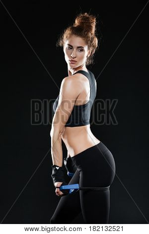 Vertical image of a Young Female fighter posing with expander over black background. Side view