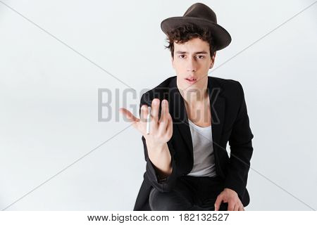 Surprised Man in suit and hat sitting in studio and holding cigarette while looking at the camera over white background