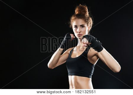 Calm female fighter ready to fight while looking at the camera over black background