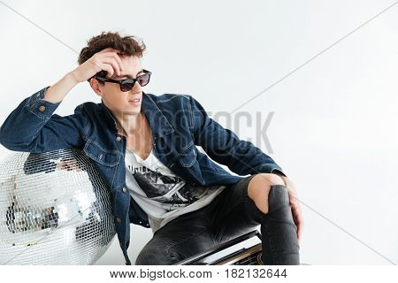 Picture of concentrated young man wearing sunglasses sitting isolated over white background near disco ball and boombox. Looking aside.
