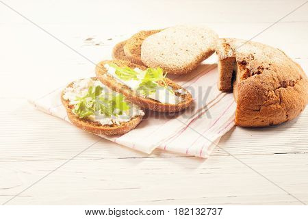 Rye bread with soft cheese and greens. Composition in rural style white ware on a white wooden table. The food lies on a napkin from fabric. Selective focus toned