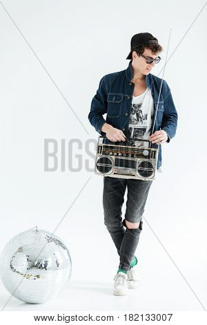 Image of cheerful young man wearing glasses standing isolated over white background and holding boombox near disco ball. Looking aside.