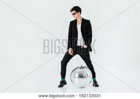 Full length portrait of a man in suit posing in studio with disco ball over white background