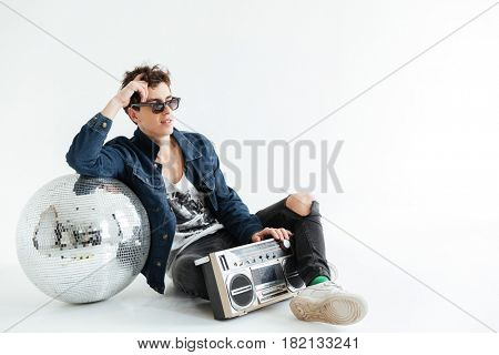 Picture of handsome young man wearing sunglasses sitting isolated over white background near disco ball and boombox. Looking aside.
