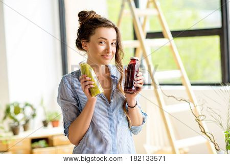 Portait of a beautiful happy woman with smoothie drinks in bottles at home. Healthy drinks concept