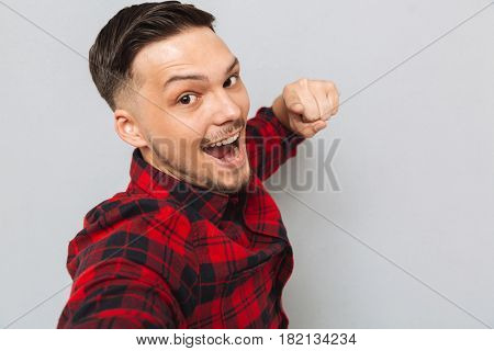 Smiling man in red shirt standing sideways and pointing at the camera over gray background. Close up portrait
