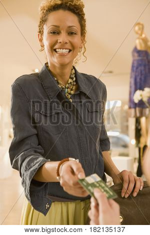 Mixed race woman handing credit card to cashier