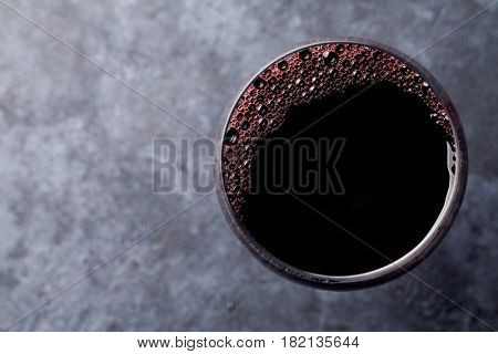 Red wine glass on stone table. Top view with copy space for your text