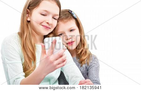 Portrait of two attractive girls, taking selfie on mobile phone,  isolated on white background