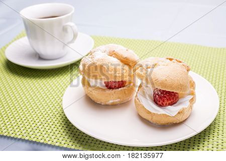 Cream puff with strawberry on white plate in front of cup