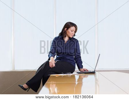 Hispanic businesswoman working in conference room