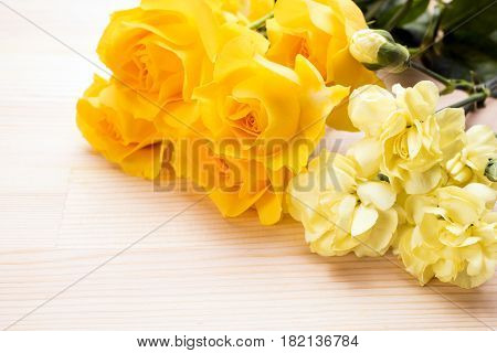 Yellow roses and carnations on a wooden table