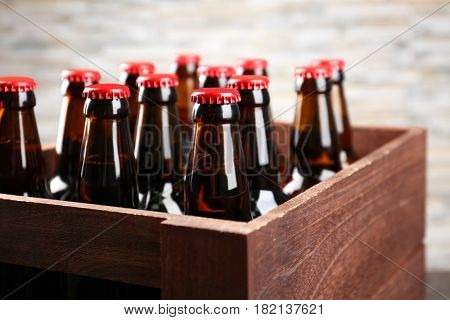 Box with bottles of beer on blurred background