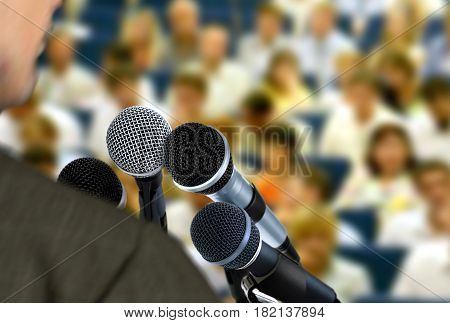 Man giving speech during seminar with blur audiance in background