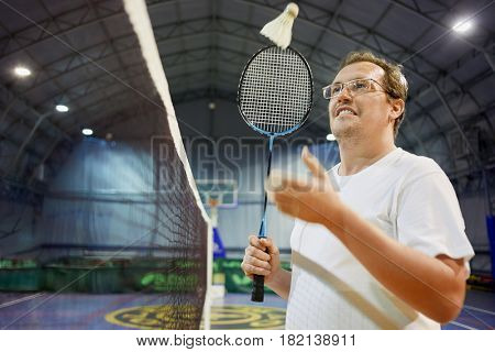 Smiling man in glasses with badminton racket throws up  shuttlecock near net at sports ground.