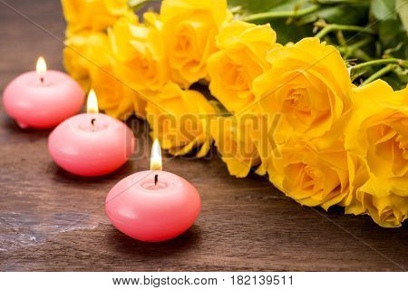 Pink candles with fire side by side yellow rose flowers