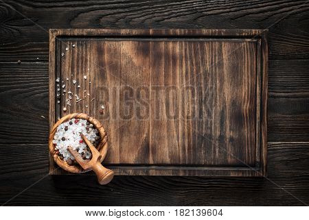 Food background. Cutting board with sea salt and pepper on dark wooden table. Copy space.