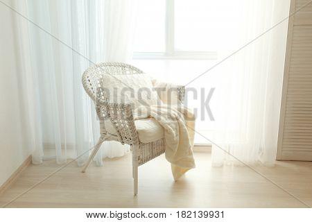 Comfortable wicker arm-chair near window in flat