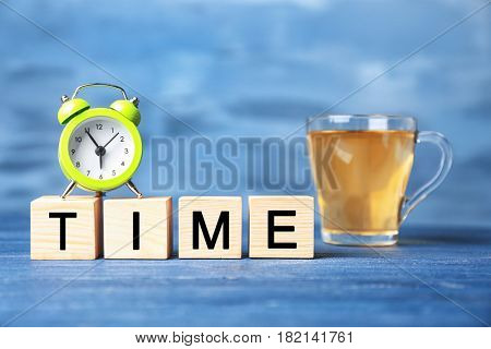 Cubes with alarm clock and cup of tea on color background. Time concept