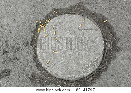 Cigarette butts on manhole