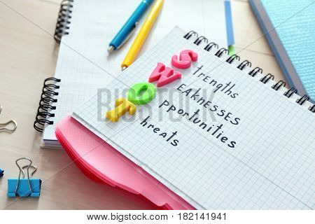 Notebook with written text STRENGTHS WEAKNESSES OPPORTUNITIES THREATS on wooden table