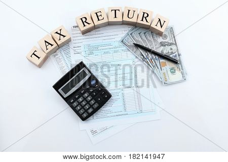 Wooden cubes with calculator, documents and money on white background. Concept tax return