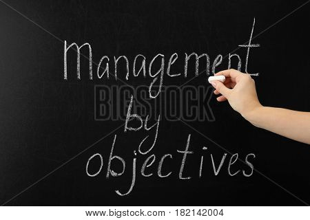 Female hand writing text MANAGEMENT BY OBJECTIVES on chalkboard