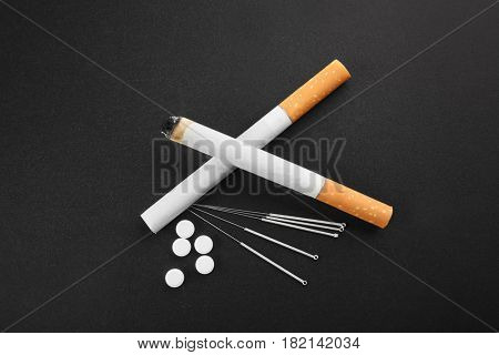 Cigarettes with needles and pills on table
