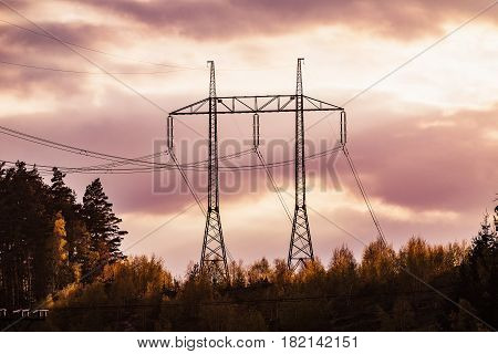 electricity transmission pylon silhouetted against red sky at dusk