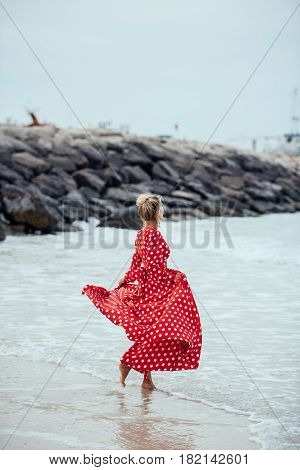 Beautiful young woman in long red dress runs along the beach. Girl in red dress. Long red dress flutters in the wind