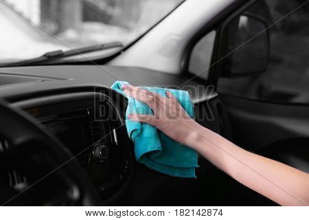 Female hand with rag cleaning dashboard in car