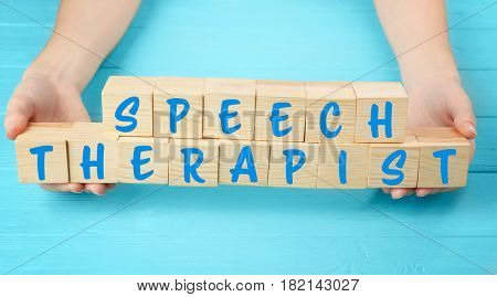 Speech therapy concept. Hands holding cubes on wooden background
