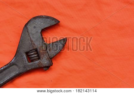 Adjustable Wrench Against The Background Of An Orange Signal Worker Shirt