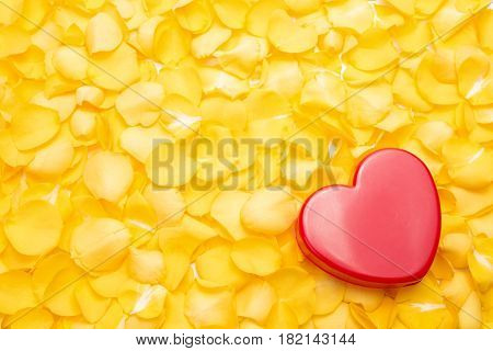 Red heart on a pile of yellow rose petals