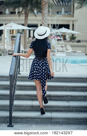 A girl with long straight hair in a blue dress with polka dots a white hat and black high-heeled shoes walking up the stairs