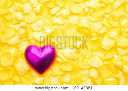 Pink heart on a pile of yellow rose petals