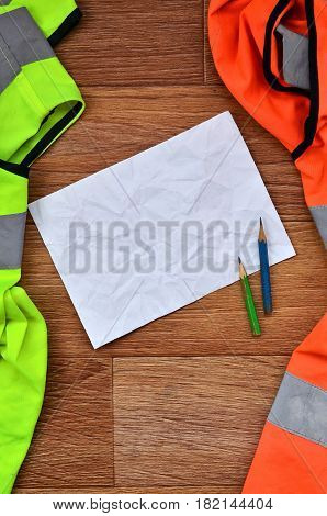 A Crumpled Sheet Of Paper With Two Pencils Surrounded By Green And Orange Working Uniforms