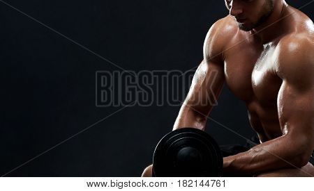 Horizontal cropped shot of a shirtless man with strong muscular sexy torso working out with a dumbbell doing biceps exercise on black background copyspace fitness gym athletics physique strength.
