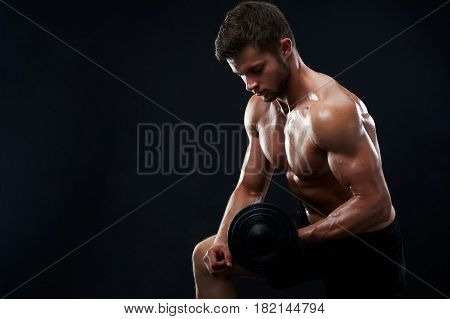 Handsome young shirtless athletic man with perfect sexy hot strong body lifting weights exercising with dumbbells on black background copyspace fitness toning shaping healthy lifestyle sport gym.
