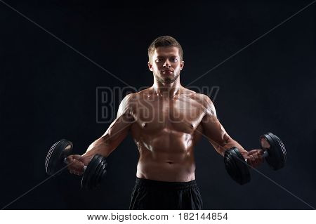 Shirtless young handsome athletic man with strong muscular ripped body working out with dumbbells on black background fitness sports motivation energy effort muscles body care gym concept.