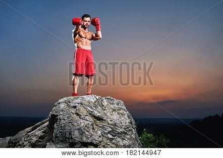 Handsome young muscular boxer with stunning hot sexy ripped body standing on a rock outdoors on sunset copyspace sports motivation lifestyle muscles toned strength toughness masculinity concept.