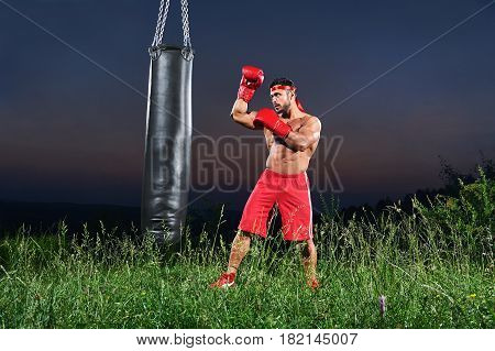 Full length shot of a young muscular strong boxer training outdoors with a punching bag copyspace nature concentration sports strength preparation achieving workout exercising confidence concept .