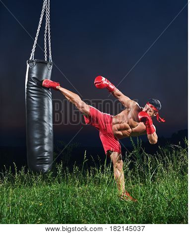 Handsome young strong muscular fighter exercising with a punching bag practicing his high kick martial arts combat fighting kickboxing Muay Thai strength power masculinity energy effort athlete.