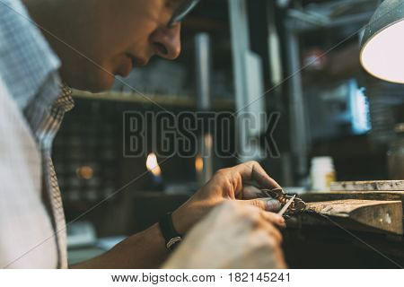 Jeweler polishing jewelry with tools at shop