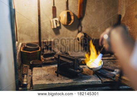 Jeweler melting gold and making jewelry in shop