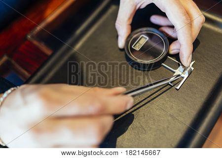 Jeweler checking diameter of diamond at shop