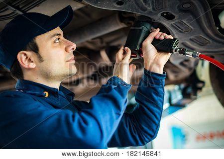 Mechanic changing car wheel in auto repair shop