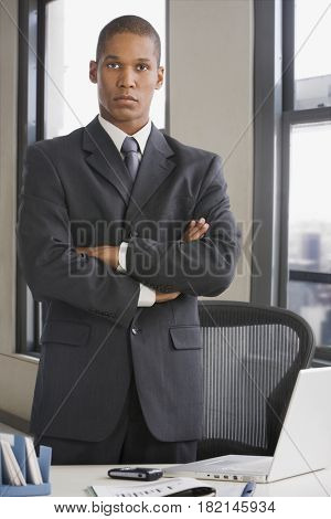 Mixed race businessman standing with arms crossed